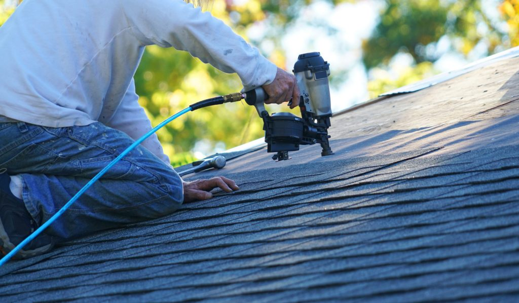 Castle Roofing – roofer nailing shingles